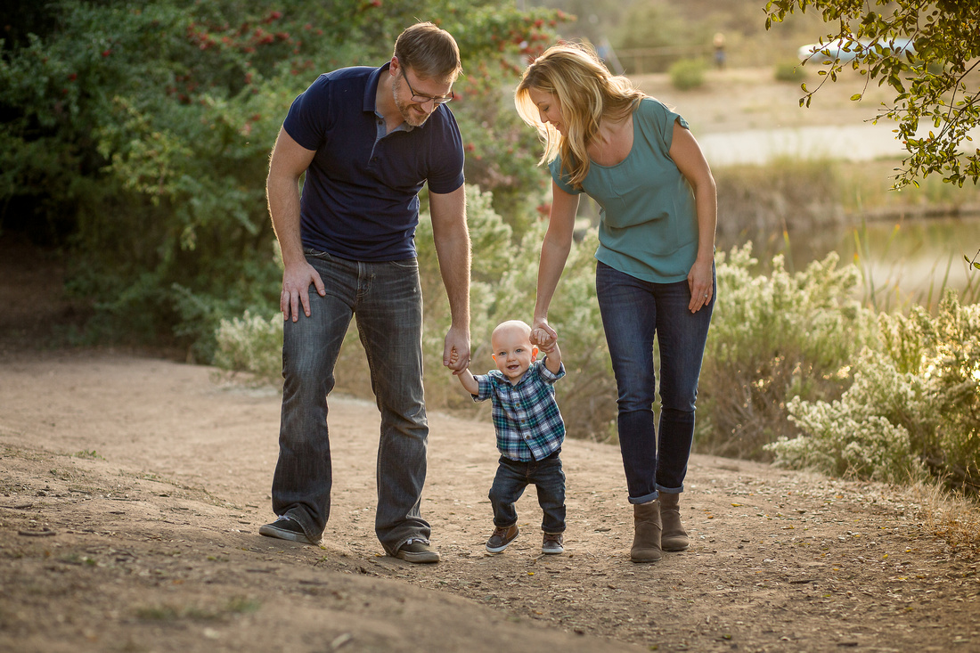 Young family holds hands walking by a lake.